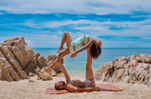 Couple doing yoga at the beach