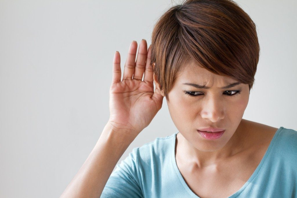 a woman suffers from hearing impairment