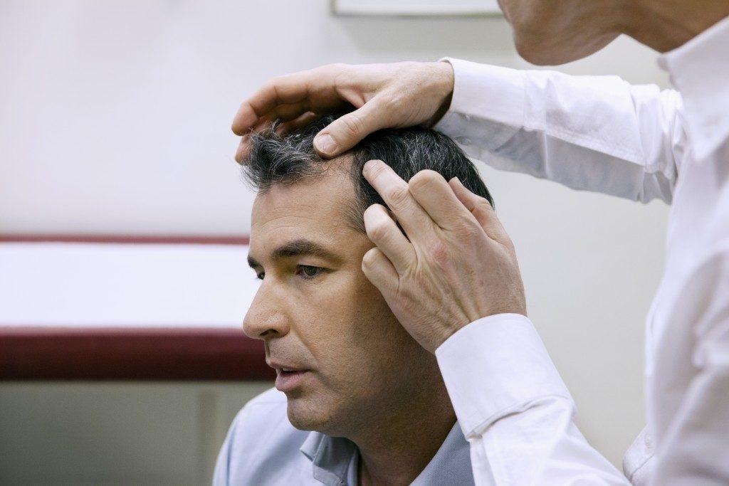man having scalp checked
