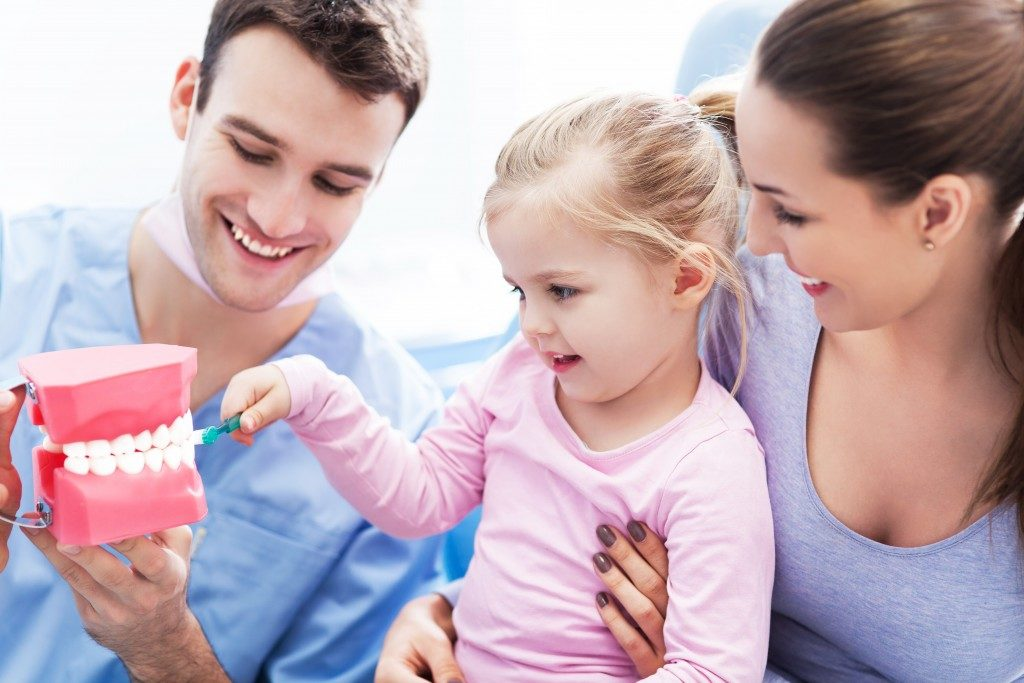 Dentist and parent teaching child how to brush teeth