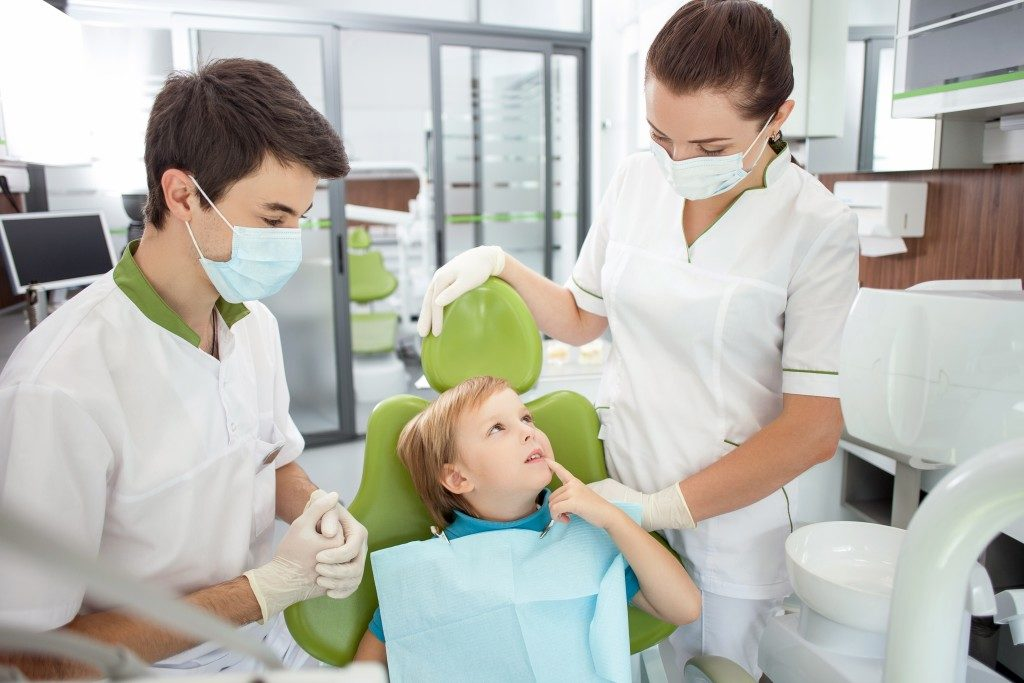 Child on a dental chair with dentists
