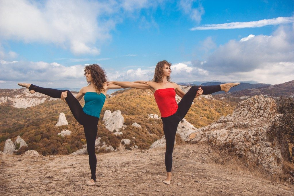 Two girls are doing acro yoga in mountains landscape