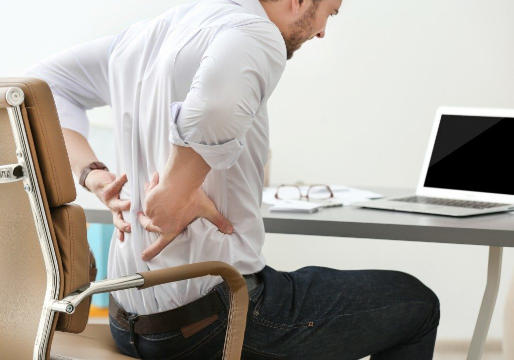Man with backpain while sitting in his desk