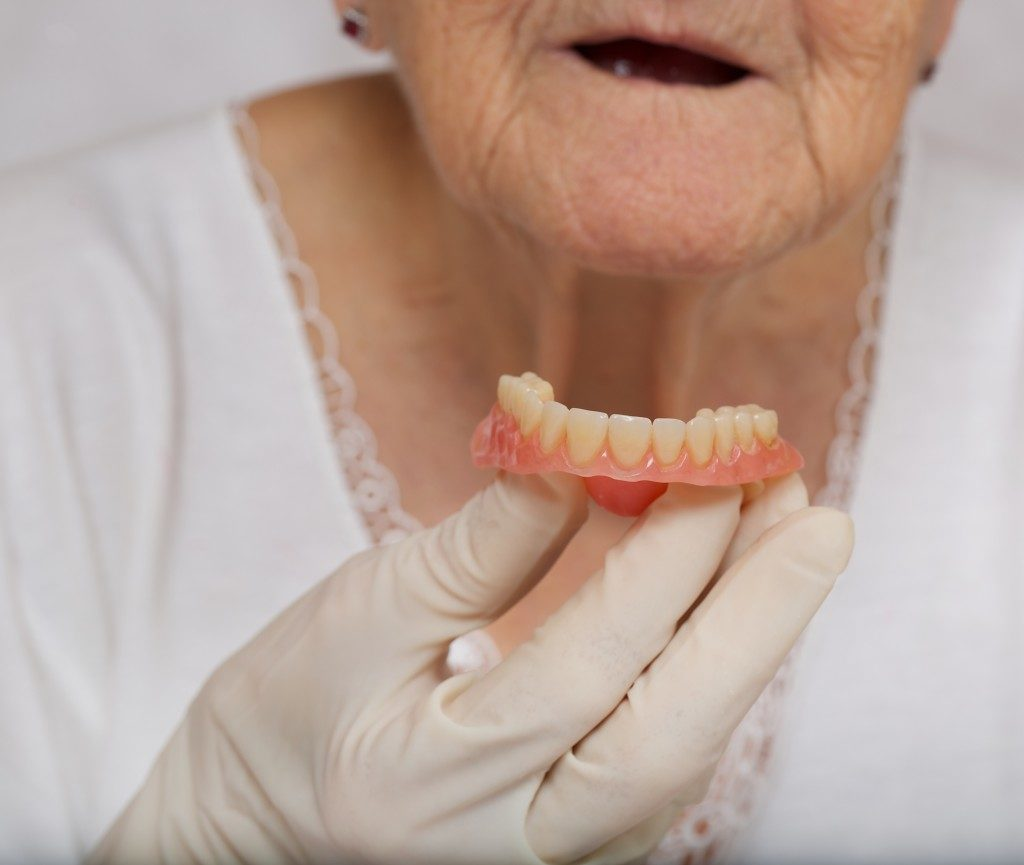elderly woman holding dentures