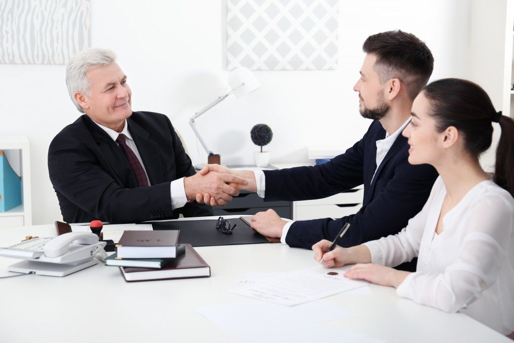 insurance agent shaking hands with couple