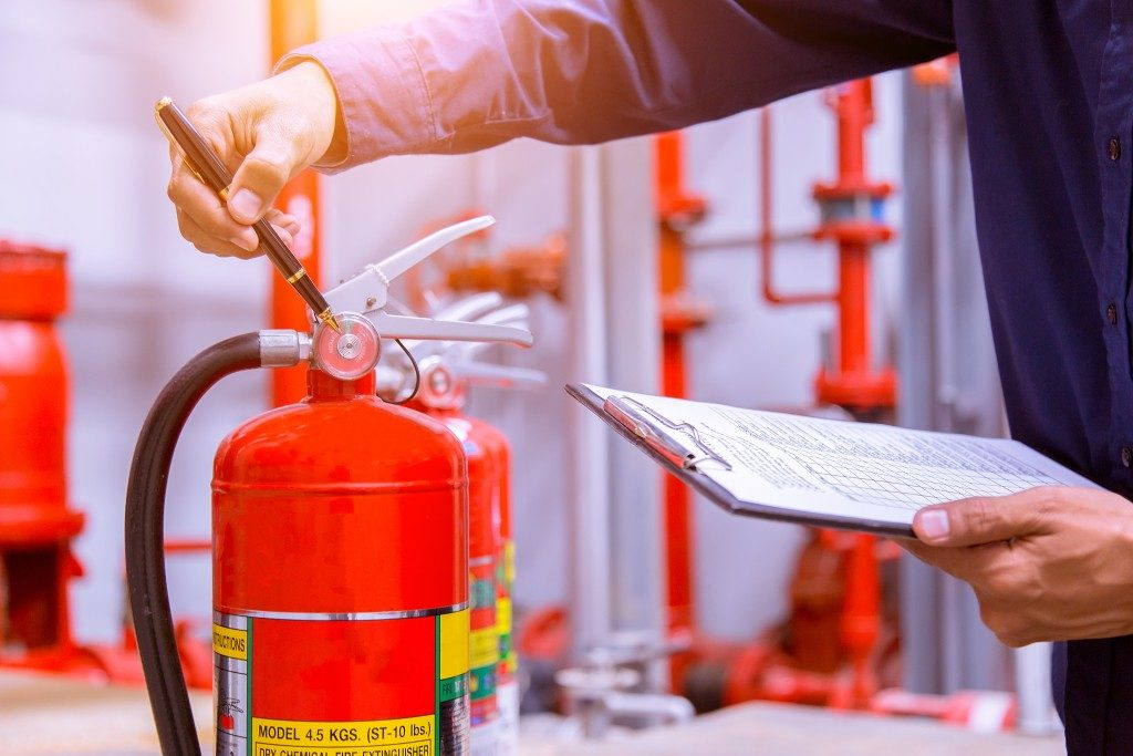 person checking fire extinguisher