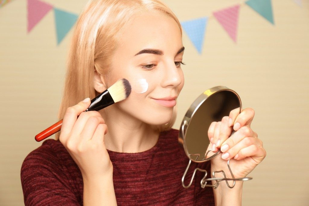 Woman using a makeup brush