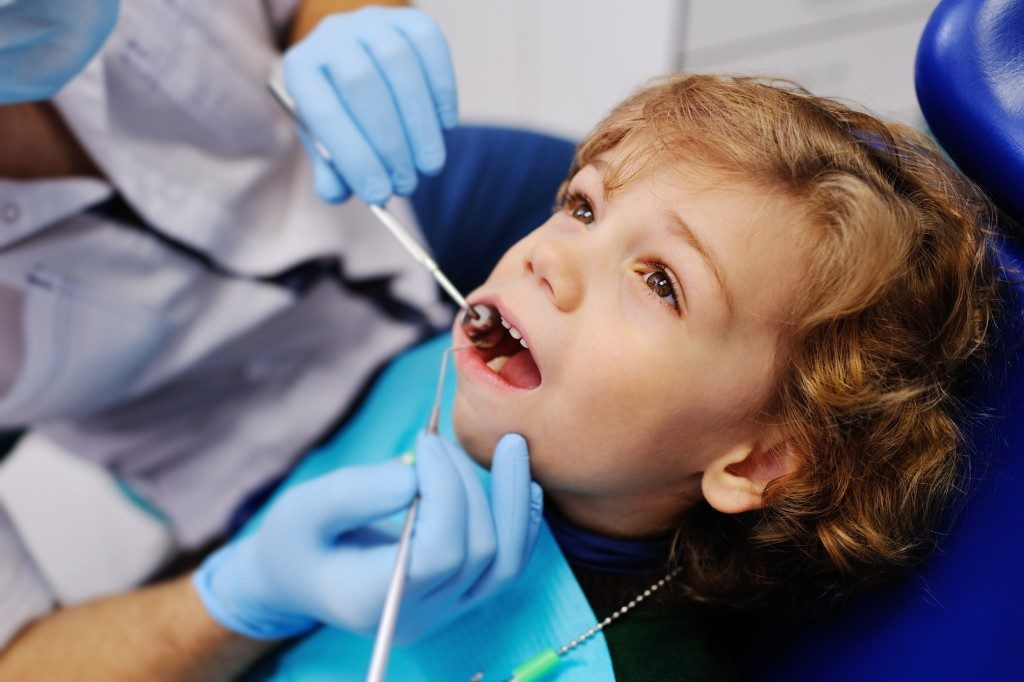 kid having his teeth checked at the dental office