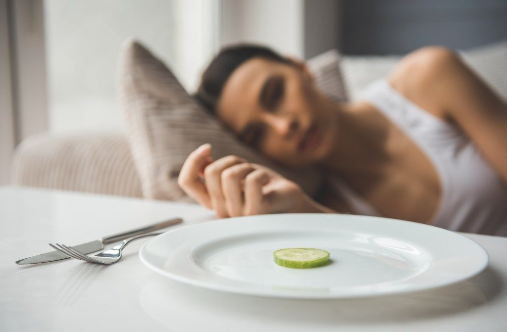 woman laying on the sofa looking dull staring at a piece of cucumber on the plate