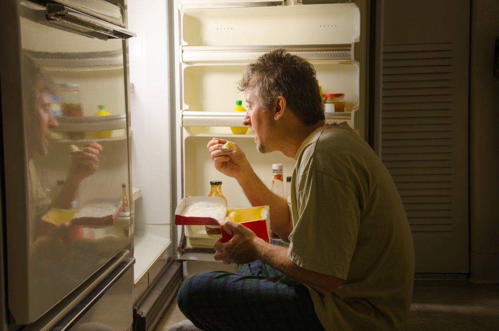 man eating late at night at the front of an open refrigerator
