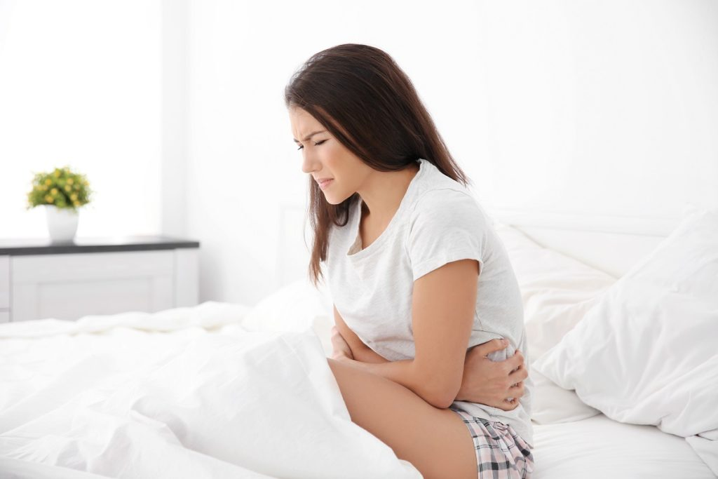 Woman in bed having bad cramps
