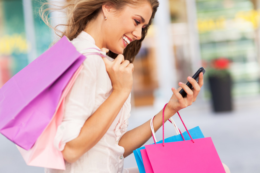 Woman texting while holding shopping bags